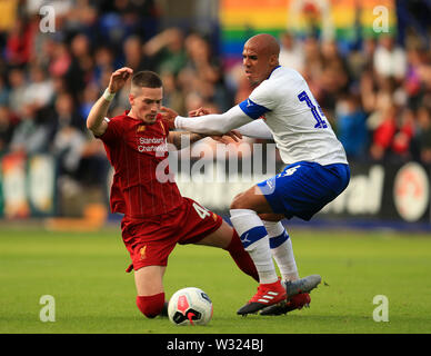 Birkenhead, Wirral, UK. 11th July 2019; Prenton Park, Tranmere, England; Pre-season friendly football, Tranmere versus Liverpool; Ryan Kent of Liverpool is tackled by Jake Caprice of Tranmere Rovers Credit: Action Plus Sports Images/Alamy Live News - Stock Image
