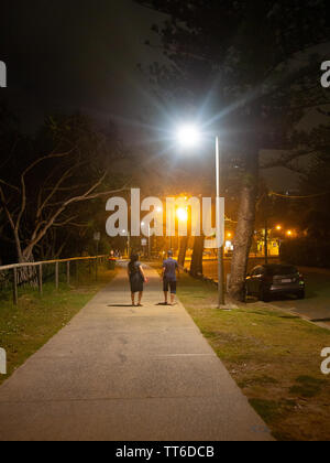 People Out For A Night Time Walk Under A Street Light - Stock Image
