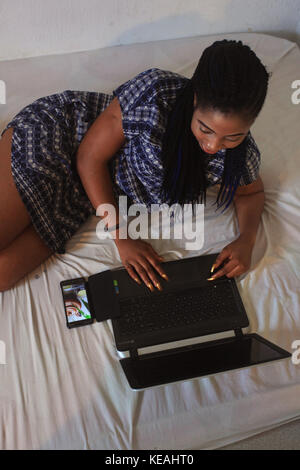 Youthful and sexy lady using new Technology for everyday living - Stock Image