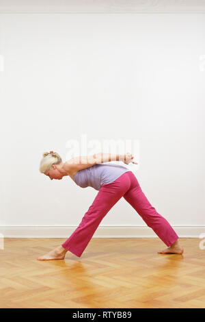 Senior woman with gray hair doing yoga exercise at home in front of a white wall, pose pyramid, copy space - Stock Image