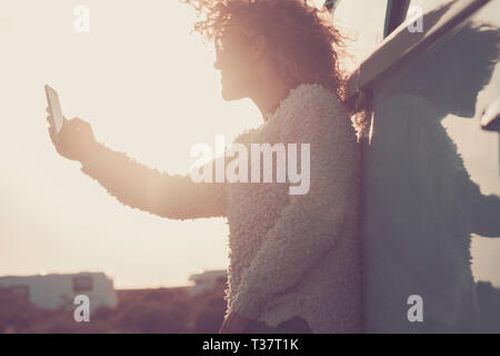 People on vacation withtechnology and vintage lifestyle and wanderlust - beautiful woman taking selfie picture with smart phone - sunset sunlight in b - Stock Image