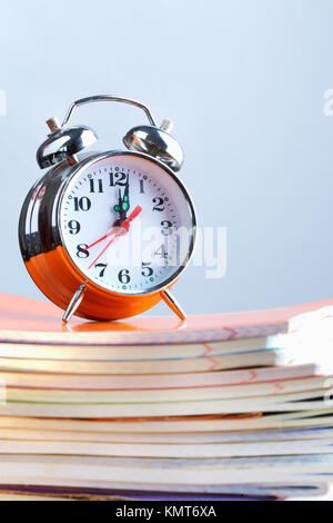 Stack of copybooks with alarm clock on its top - Stock Image