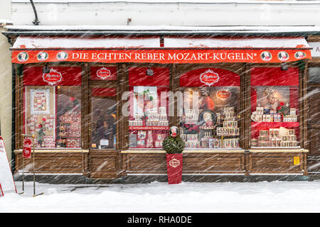 The historical and famous Echten Reber Mozart Kugeln chocolate shop in a snow day, Alter Markt Square, Salzburg, Austria - Stock Image