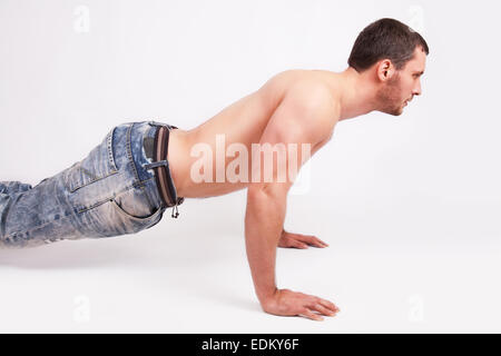 A young man pushed off the floor, studio shot - Stock Image