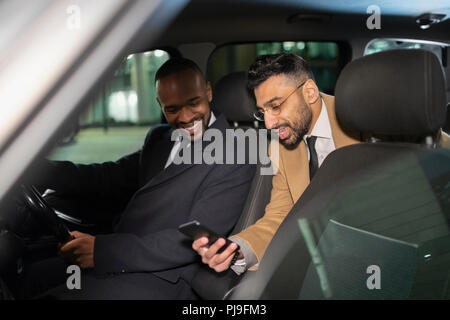 Businessman with smart phone using crowdsourced taxi - Stock Image