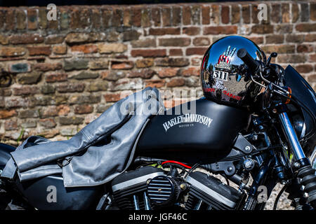 Helmet and a women's jacket on a Harley Davidson Iron 883 motorcycle. - Stock Image