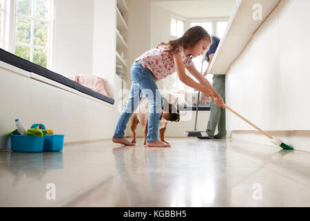 Dad and daughter sweep the kitchen floor together, side view - Stock Image