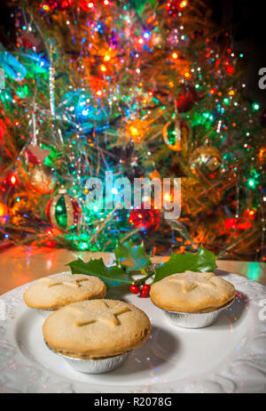 A plate of mince pies under a Chrsitmas tree. - Stock Image