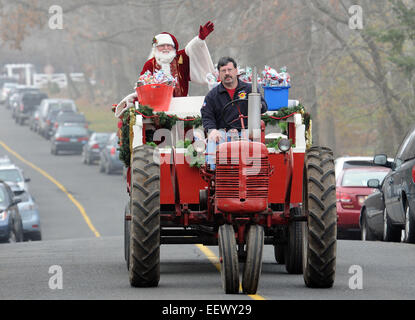 Semour CT USA-- Santa (Jim Chedister of Trumbull) gets a lift from Tom Eighmie of Seymour as Santa visited the party - Stock Image
