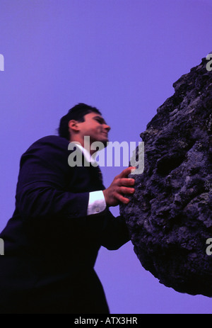Caucasian business man pushing a rock - Stock Image
