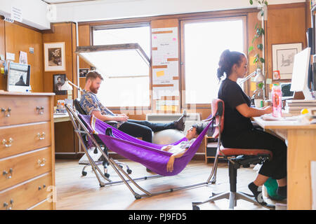 Creative designers relaxing in hammock in office - Stock Image