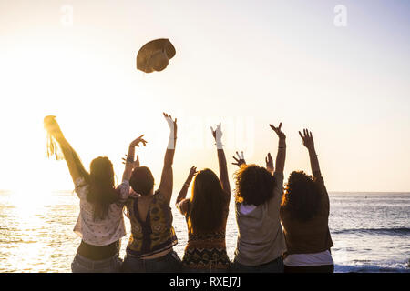 Summer and happiness for travel and freindship concept with group of happy girls viewed from rear enjoying and celebrating the sunset and the sea toge - Stock Image