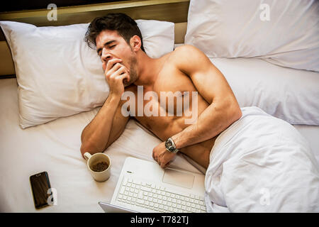 Young Handsome Shirtless Sleepy Man, Lying in Bed Yawning as He's Waking Up - Stock Image