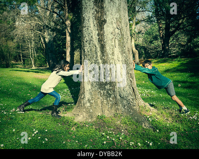 Opposing force: boy and girl push tree - Stock Image