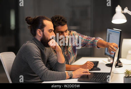 creative team with computer working late at office - Stock Image