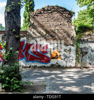 Graffiti-covered Cemetery wall with exposed brickwork & street art in Baruther strasse, Kreuzberg-Berlin - Stock Image
