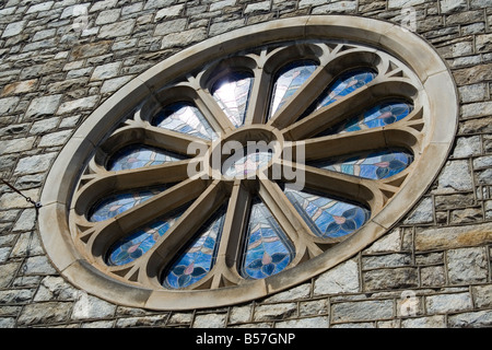 radial stainglass stain glass window color glass colour round stone wall - Stock Image