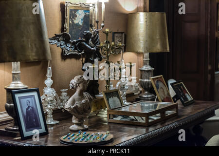 Ornaments, pictures, photographs and other artifacts on a table in a stately home. - Stock Image