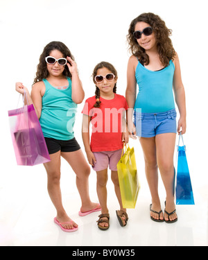three young girls with shopping bags isolated on white. - Stock Image