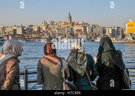 Four women in headscarves watch the scenery along the Golden Horn, in Eminönü.  Galata Tower can be seen - Stock Image