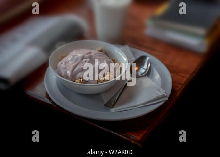Healthy breakfast on wooden table, selective focus, with books and newspaper in the background, suggesting a student or businessperson in a café, angl - Stock Image