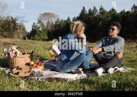 man and woman share gifts for valentines under the sun on picnic day - Stock Image