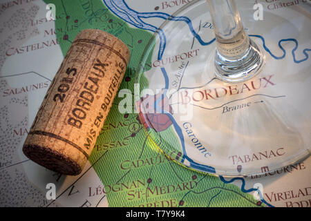 Bordeaux French wine tour tasting concept, with wine glass stem, vintage year 2015 Bordeaux cork in close up, on old historic Bordeaux wine areas map - Stock Image