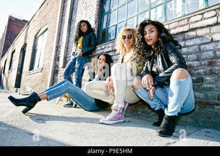 Four young women with curly hair sitting side by side on steps outside a building. - Stock Image