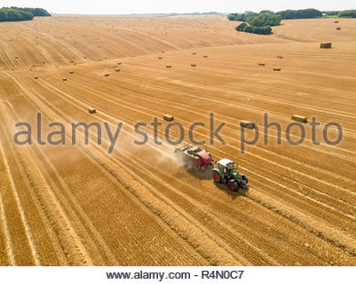Aerial overhead of tractor baler straw bales in field after wheat harvest in summer on farm - Stock Image