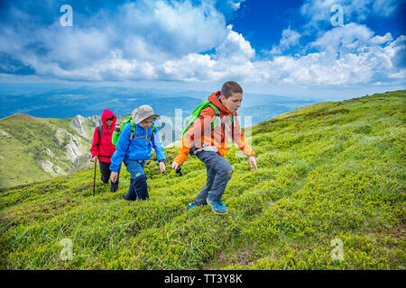 Two kids are hiking with their mother on the mountain - Stock Image