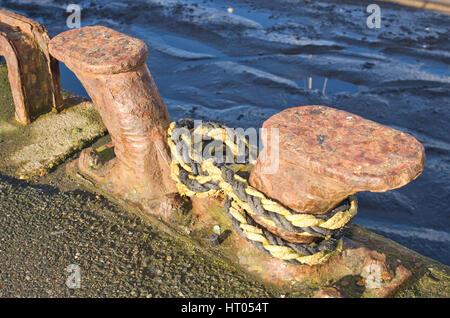 Rope fastened to bollard - Stock Image