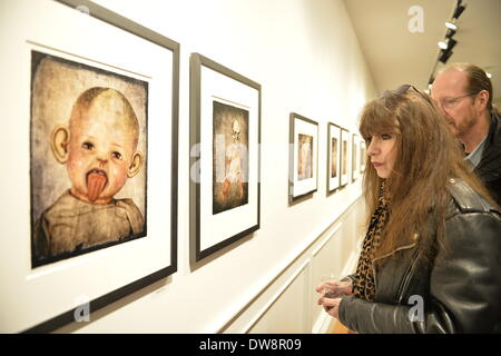 Huntington, New York, U.S. - March 1, 2014 - GAIL NELSON and BILLY NELSON, of Freeport, look at the humorous artwork of a baby doll sticking out its tongue, in the 'Vitreous Humor – A Collection of Absurd Images' exhibit that combines photos of dolls with vintage medical illustrations, by artist Lois Youmans at the FotoFoto Gallery Opening  Reception 'Artists reception '3 Wild & Crazy Artists.' © Ann E Parry/Alamy Live News - Stock Image
