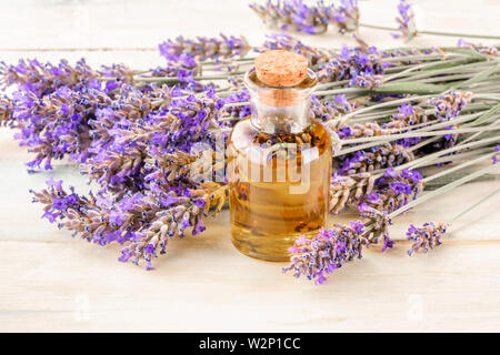 Lavender essential oil with a bouquet of flowers, toned image - Stock Image