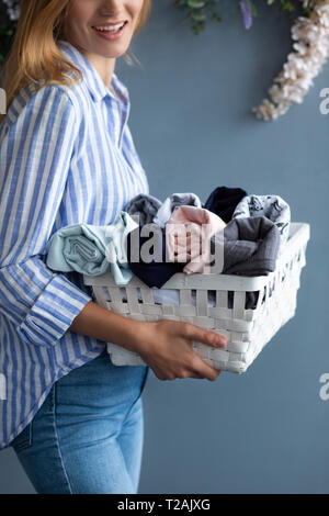 Woman carrying basket of fabrics - Stock Image
