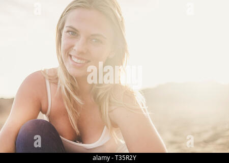 Cheerful portrait of beautiful young blonde girl smiling and enjoying the outdoor - sexy woman with long hair and sun backlight in backgorund - Stock Image