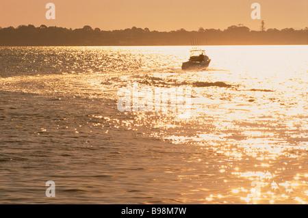 Boat motoring out to sea Moreton Bay Queensland Australia - Stock Image