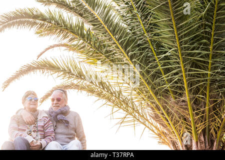 Happy old senior caucasian couple hug and stay in love together in retired lifestyle under a tropical palm - white clear sky in background - fashion p - Stock Image