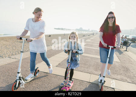 Lesbian couple and daughter riding push scooters on sunny beach - Stock Image