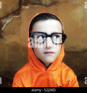 Young boy with black glasses  looking away - Stock Image