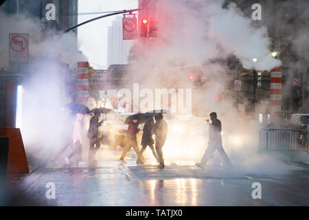Undefined people with umbrellas are crossing the 42nd street in Manhattan. Steam coming out from from the manholes in the background. - Stock Image