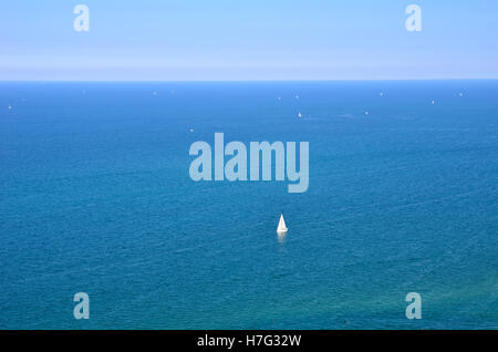 A solitary sailing boat in the sea - Stock Image