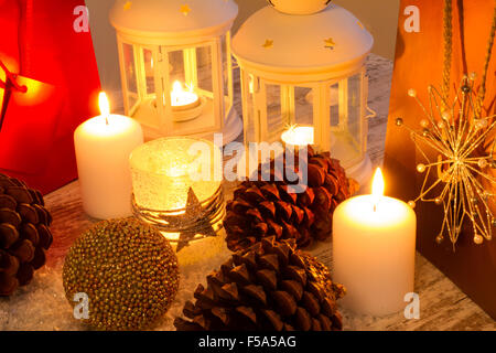 Christmas setting with candles, pine cones, shopping bags and baubles. - Stock Image