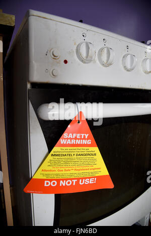 Unsafe gas cooker with safety warning notice, UK - Stock Image