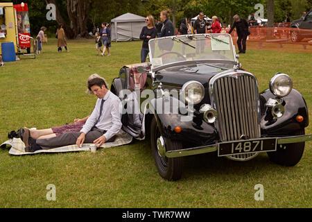 Couple sitting near their vintage Singer motor car - Stock Image