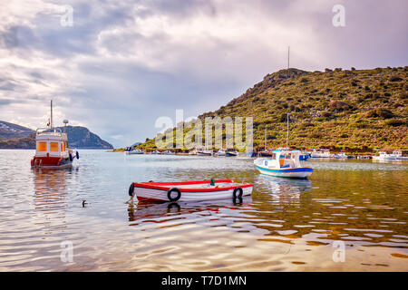 Yachts and boats anchored over the calm sea at gumsuluk bay in Bodrum, Mugla, Turkey. - Stock Image