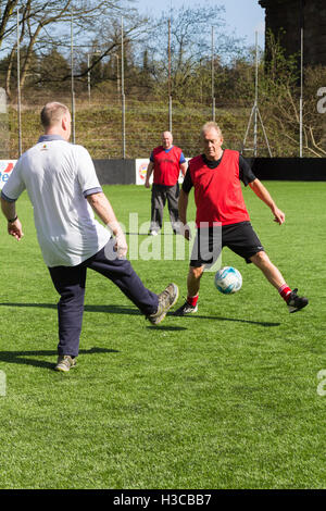 Middle-aged man taking part in a walking football session in Bolton, Lancashire, organised by the Bolton Wanderers - Stock Image