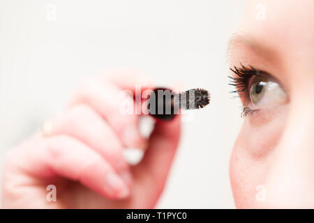 Caucasion 30 year old woman putting on makeup. - Stock Image