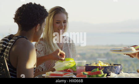 Selective focus view of couple eating outdoors near scenic view of remote landscape - Stock Image