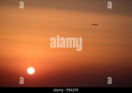 Airplane ( Aeroplane ) passing by a setting sun with gorgeous orange and red sky to its destination, East Attica, Greece, Europe. - Stock Image