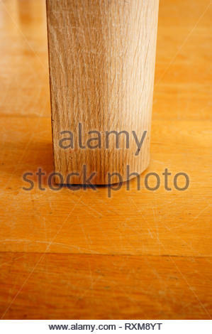 Wooden leg of a table on a parquet floor. - Stock Image